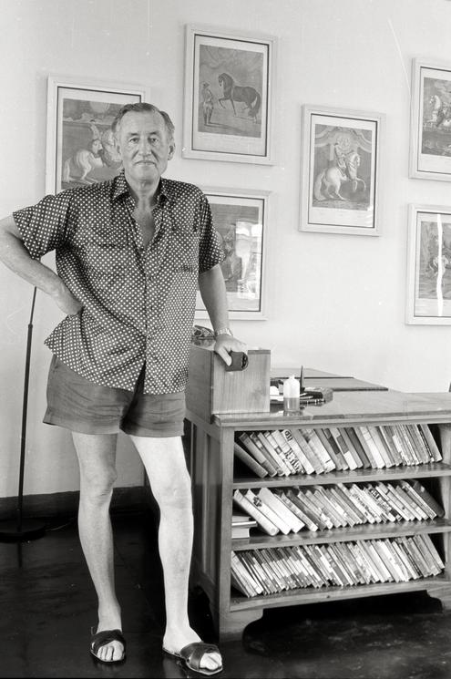 Ian Fleming samen met een aantal eerste edities boeken die hij verzamelende